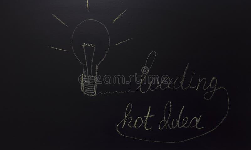 Utdraget ljus på svart tavla med texten: varm idé och päfyllning royaltyfria foton