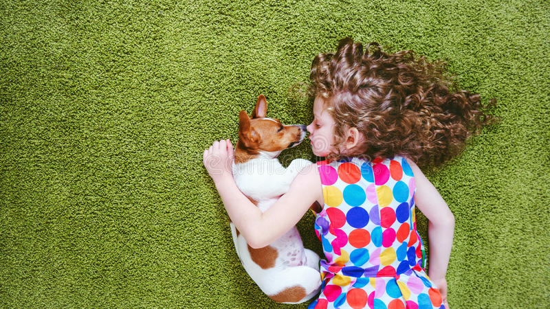 Ute child with puppy jack russell sleeping on the green carpet. royalty free stock photos