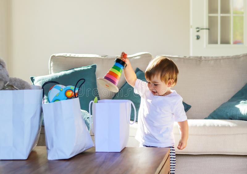 Ute happy smaling baby boy unpacking gifts toys out of shopping bags at home. royalty free stock images