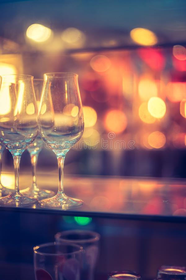 Uteliv: Vinexponeringsglas och f?rgglade ljus i en nattklubb royaltyfri foto