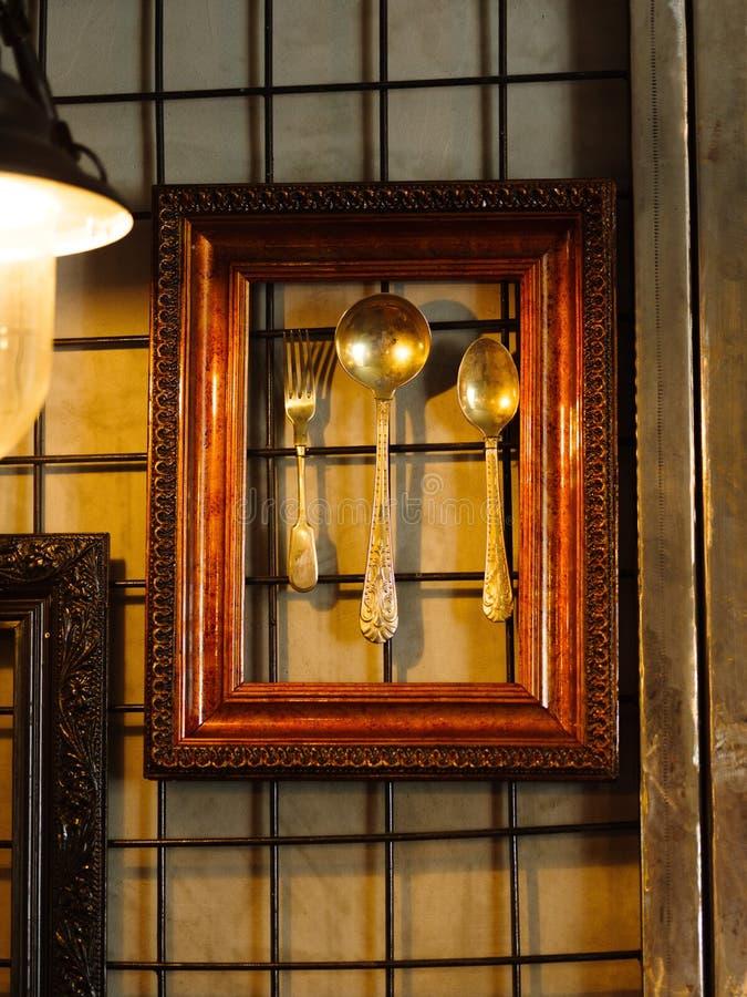 Utensílio brilhante em um fundo da parede Colheres de prata e pouco para imagens de stock