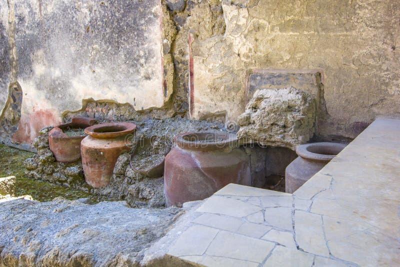 Utensílios antigos da cozinha - potenciômetros, vasos das escavações/ruínas da cidade velha de Pompeii, Nápoles, Itália fotos de stock royalty free
