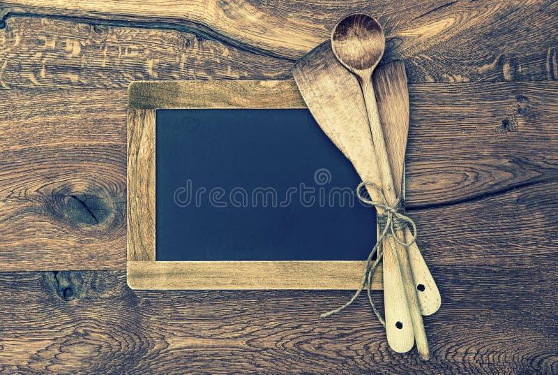 Utensílios da cozinha e quadro-negro do vintage no fundo de madeira imagens de stock