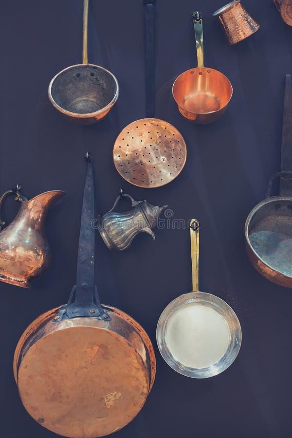 Utensílios da cozinha pendurados na parede preta imagem de stock