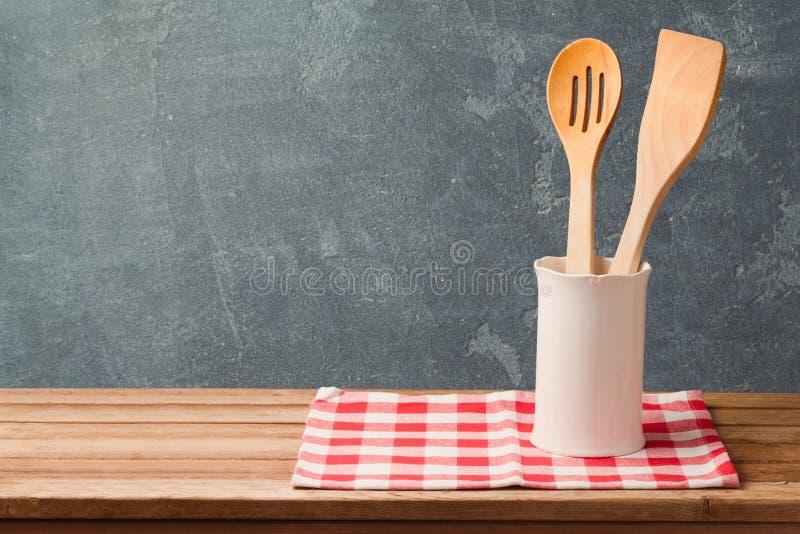 Utensílios de madeira da cozinha na tabela com toalha de mesa sobre o fundo do quadro-negro com espaço da cópia fotografia de stock royalty free