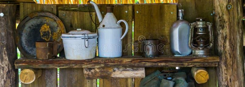 Utensílios de mesa velhos do vintage em uma prateleira de madeira, em alguns copos velhos oxidados e no equipamento das placas, o imagem de stock