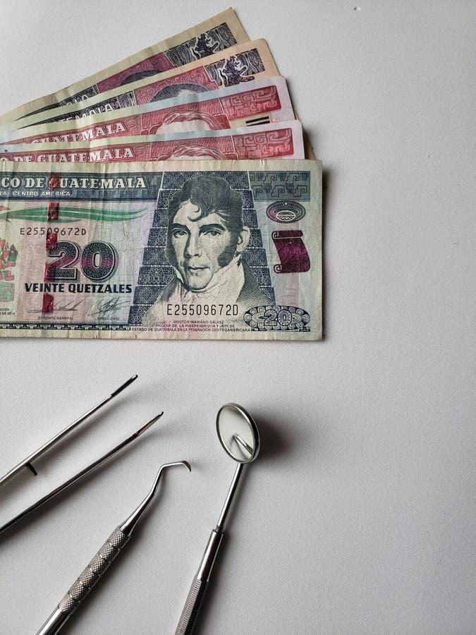 utensílios do dentista para a revisão oral e cédulas guatemaltecas imagem de stock