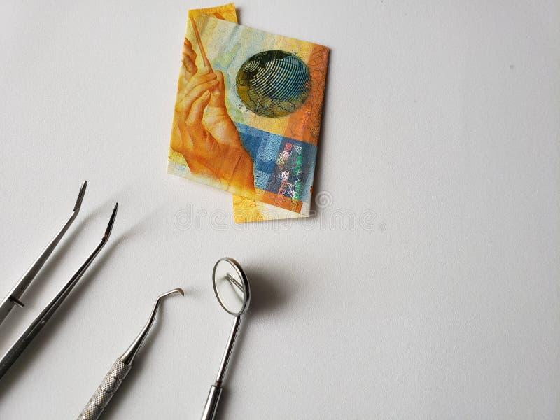 utensílios do dentista para a revisão oral e uma cédula suíça de dez francos fotos de stock