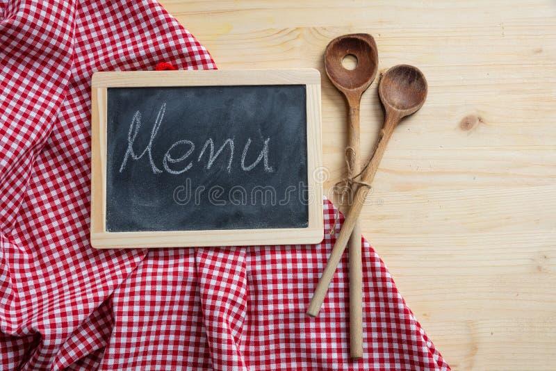 Utensílios do quadro-negro e da cozinha na toalha de mesa vermelha, tabela de madeira, espaço para o texto, vista superior imagem de stock royalty free