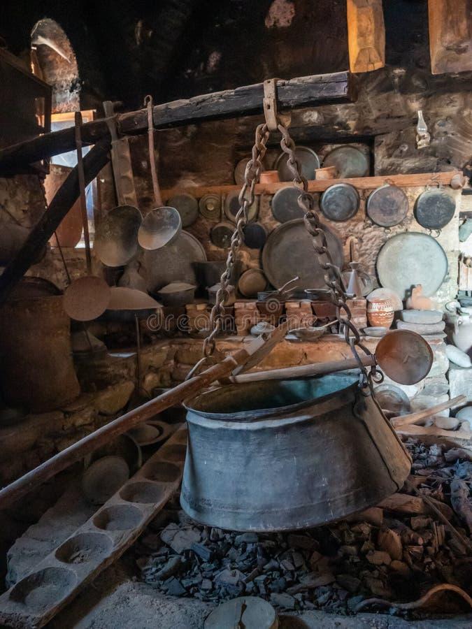 Utensílios e lareira antigos com uma caldeira na cozinha antiga no monastério na região de Meteora, Grécia de Megala Meteora imagens de stock royalty free
