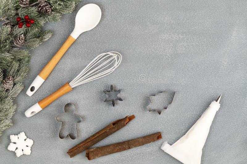 Utensierung zum Weihnachtskochen oder Backen mit Löffel, Whisk, Eisrohrsack und Keksschneider mit Tannenverschluss auf Beton lizenzfreie stockbilder