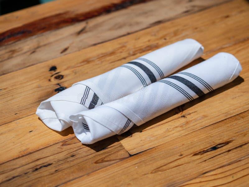 Utensili acciambellati in tovagliolo per le cene ad un ristorante all'aperto fotografia stock