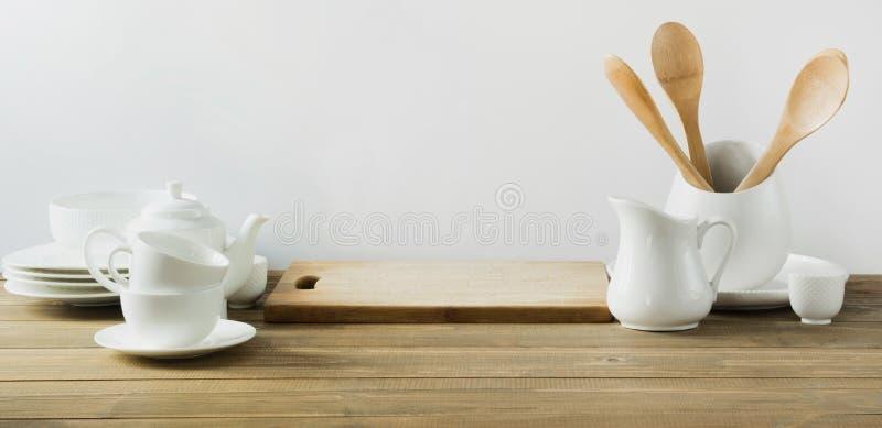 Utensili bianchi della cucina, stoviglie e l'altra roba bianca differente per servire sul bordo di legno bianco fotografia stock libera da diritti