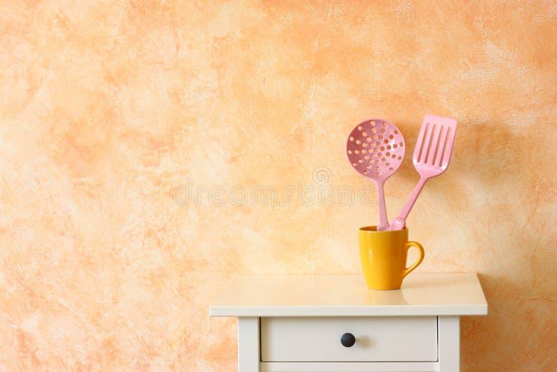 Utensili da cucina della cucina. spatole di plastica in tazza gialla contro la parete rustica di terracotta. fotografie stock libere da diritti