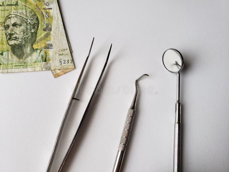 utensili del dentista per la rassegna orale e una banconota tunisina di cinque dinari fotografia stock