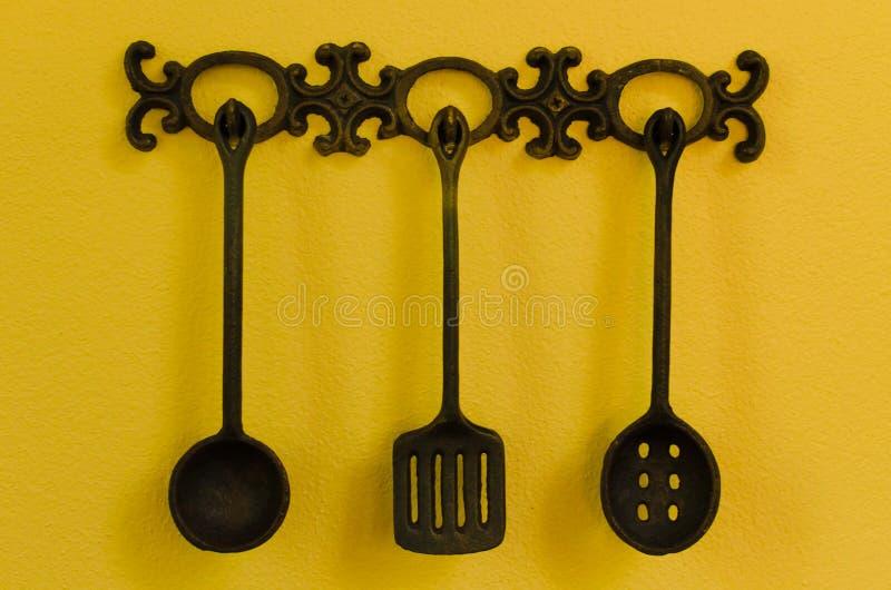 Utensili della cucina che appendono sul fondo giallo fotografia stock