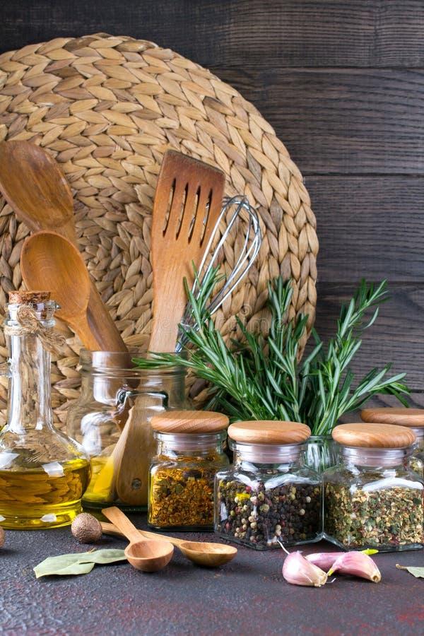 Utensili della cucina, erbe, spezie asciutte variopinte in barattoli di vetro su buio fotografia stock