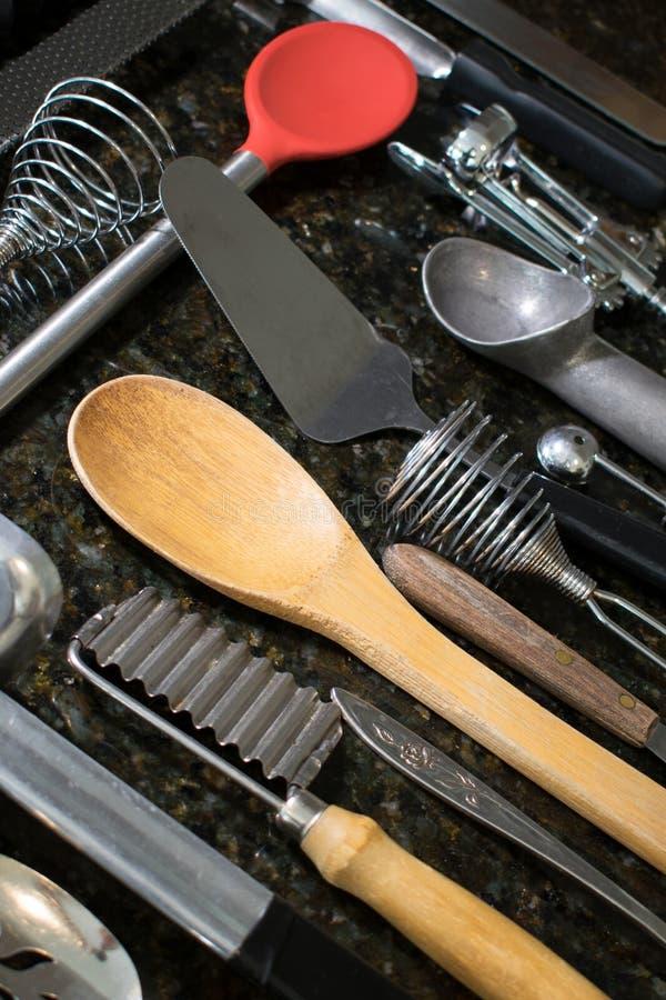 Utensili della cucina sistemati sulla superficie del nero fotografia stock libera da diritti