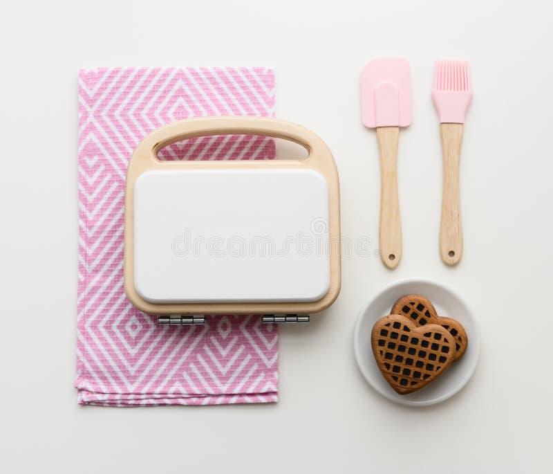 Utensili di legno alla moda della cucina del gioco Creatore, cialde, spatola e spazzola di legno della cialda sullo spazio bianco immagine stock