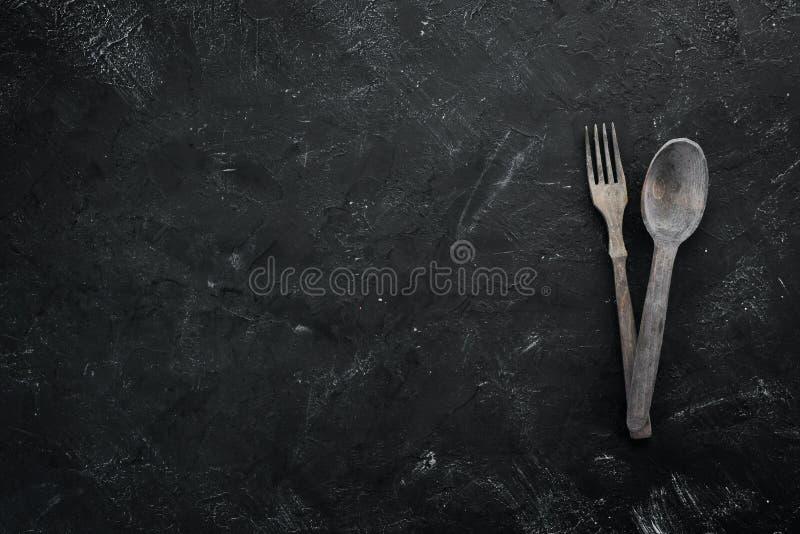 Utensili di legno della cucina Su un fondo di pietra nero fotografie stock libere da diritti