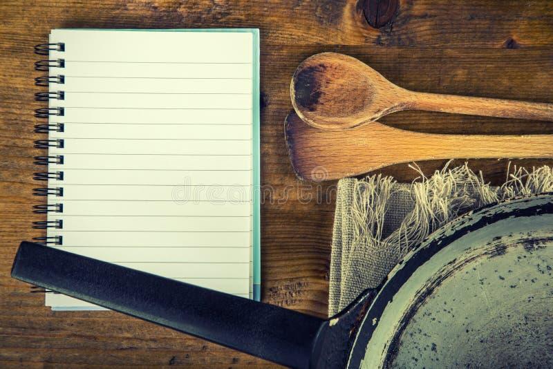 Utensili di legno della cucina sulla tavola cucchiaio di legno del libro di ricetta in un retro - Un ampolla sulla tavola ...