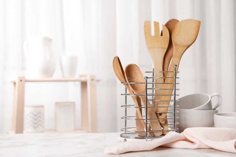 Utensili e stoviglie di legno sulla tavola in cucina fotografia stock libera da diritti