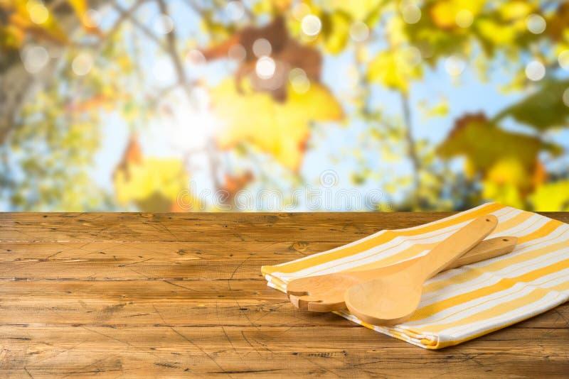 Utensili e tovaglia della cucina sulla tavola di legno sopra il fondo del bokeh di autunno fotografia stock libera da diritti
