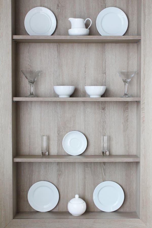 Utensili e vetri della cucina su una parete grigia immagini stock