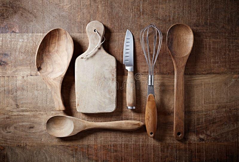 Utensilios de madera clasificados de la cocina en una superficie de madera rústica foto de archivo