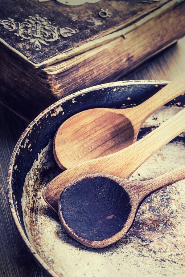 Utensilios de madera de la cocina en la tabla Cacerola vieja de la cuchara de madera del libro de la receta en un estilo retro en fotografía de archivo libre de regalías