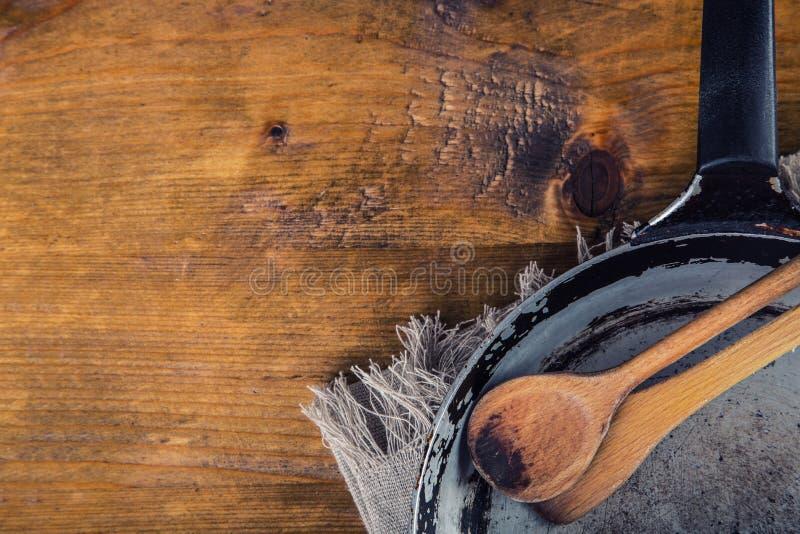Utensilios de madera de la cocina en la tabla Cuchara de madera del libro de la receta en un estilo retro en la tabla de madera imagenes de archivo