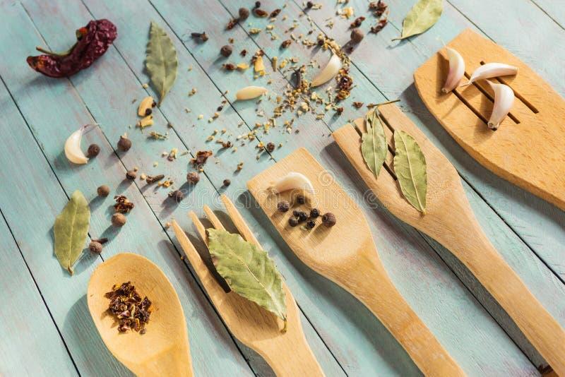 Utensilios de madera de la cocina y diversas especias encendido fotografía de archivo