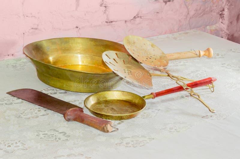 Utensilios más viejos de la cocina en la tabla contra el fondo del brickw foto de archivo libre de regalías