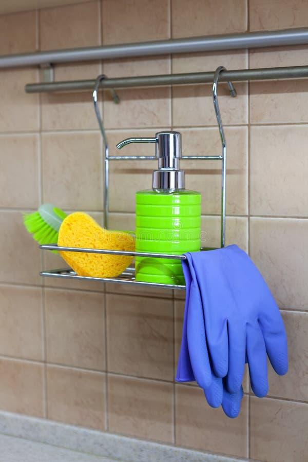 Utensilios para los platos que se lavan, líquido, guantes, cepillo, esponja en estante del metal en cocina Concepto de decantar l imagen de archivo