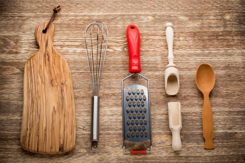Utensilios rurales de la cocina en la tabla de madera del vintage de foto de archivo