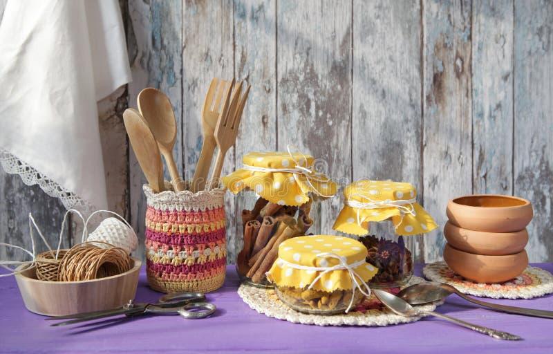 utensils för service för anddatalistkök trevliga Kanel, kryddnejlikor och gurkmeja i glass krus royaltyfria foton
