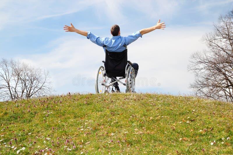 Utente di sedia a rotelle felice su una collina verde fotografia stock