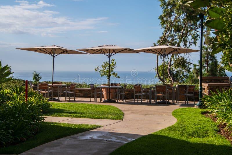 Uteplats med tre tabeller med paraplyer Det finns en stenvägg Uteplatsen förbiser havet royaltyfri fotografi