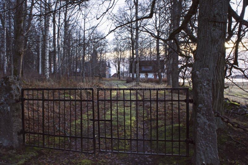 Utfärda utegångsförbud för framme av den lilla vita stugan i mystisk skog arkivbild