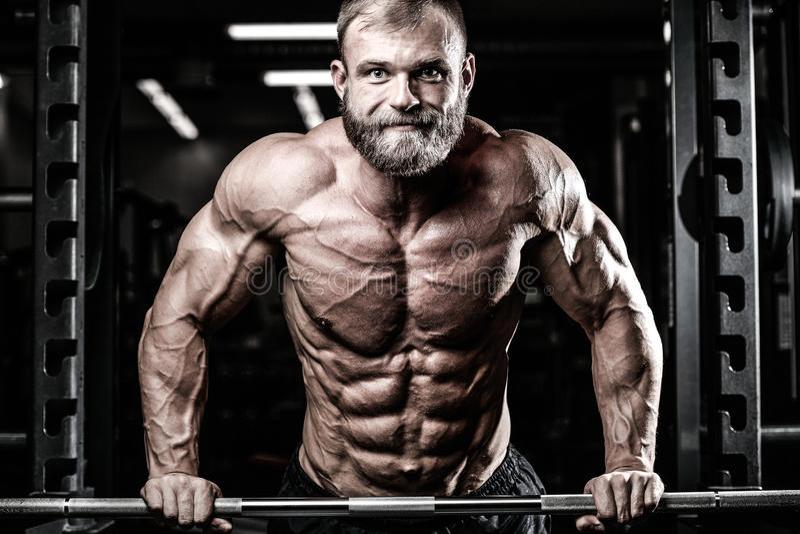 Utför den manliga modellen för Caucasian sexig kondition övning med skivstången arkivfoto