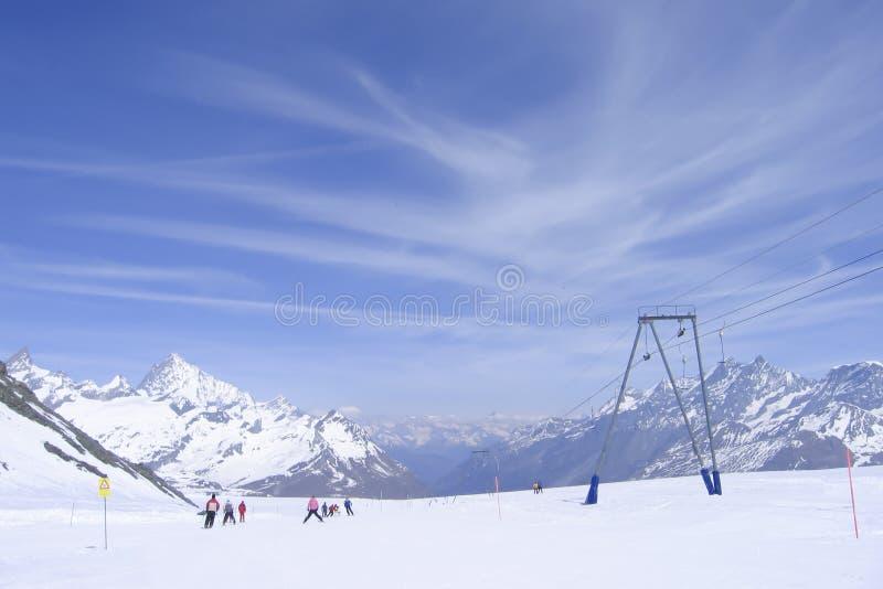 utförsåkning på förberett skidar lutningen i schweiziska fjällängar royaltyfria bilder