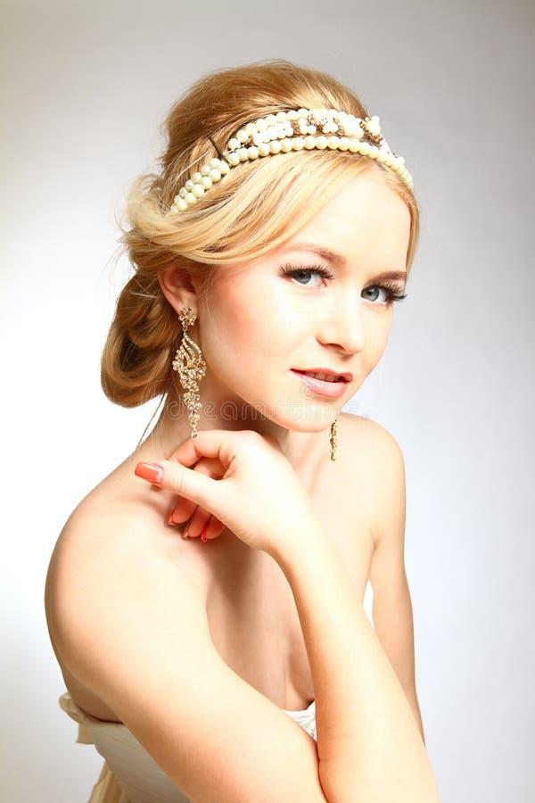 Utformade grek för den unga kvinnan för elegans på grå bakgrund royaltyfri bild