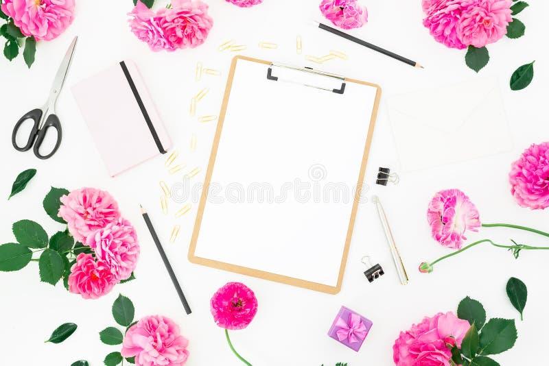 Utformat gifta sig workspace med skrivplattan, anteckningsboken, rosa rosor, ranunculusen och tillbehör på vit bakgrund Lekmanna- royaltyfria bilder