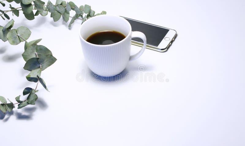 Utformat materielfoto Kvinnlig stillebensammansättning med koppen kaffe, telefonen och buketten av eukalyptuns förgrena sig på fotografering för bildbyråer