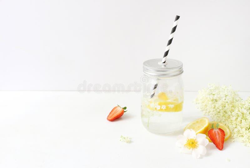 Utformat materielfoto Stillebensammansättning med hemlagad elderflowerslemonad i den glass dricka kruset, citroner arkivfoton