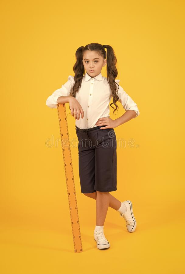 Utforska stammen Utbildning och skolkoncept Storlek och mätning Pupil söt flicka med stor linjal Geometri royaltyfri foto