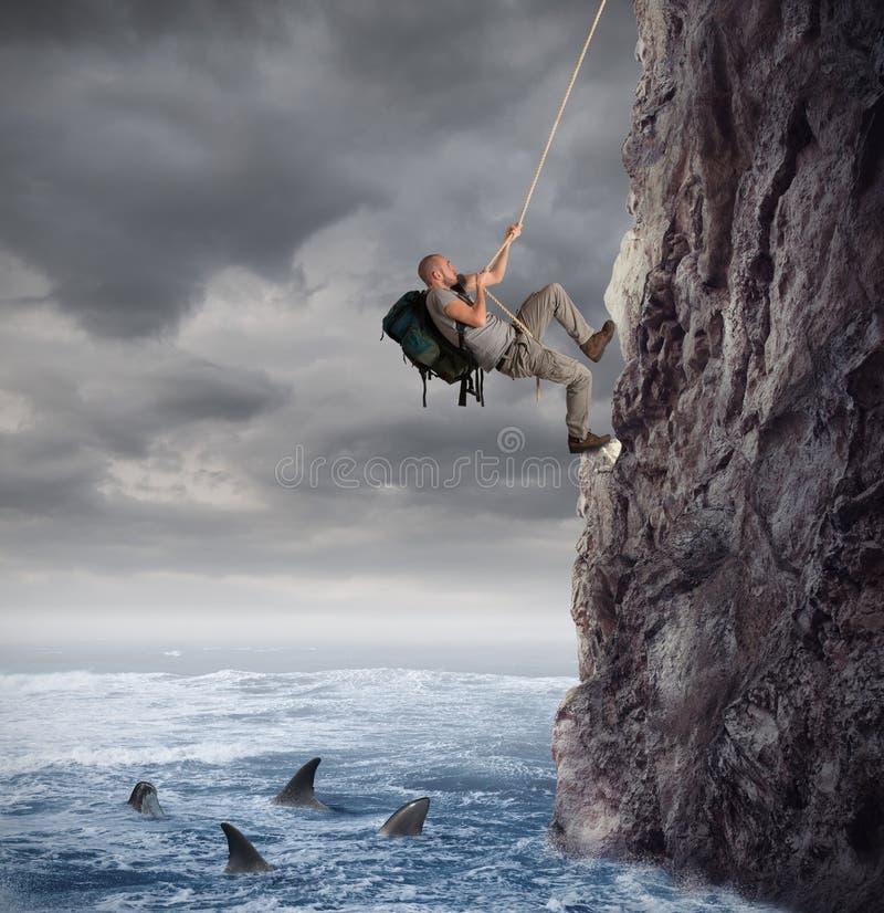 Utforskaren klättrar ett berg med risken för att falla på havet med hajar royaltyfria bilder