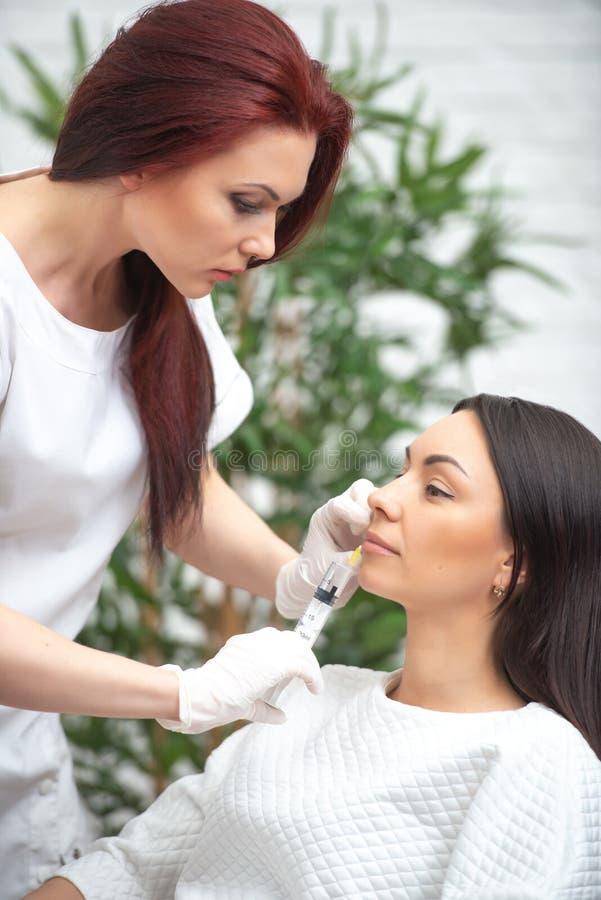 Utfyllnadsgodsinjektion för framsida Plast- estetisk ansikts- kirurgi Doktorskvinnan som ger injektioner med injektionssprutan, i arkivbilder