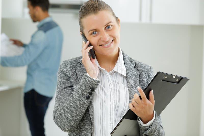 Utgående affärskvinna på telefonen som ser kameran royaltyfri fotografi