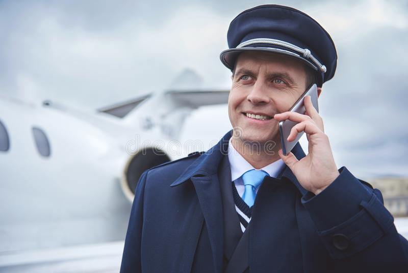 Utgående flygare som talar vid telefonen royaltyfria bilder
